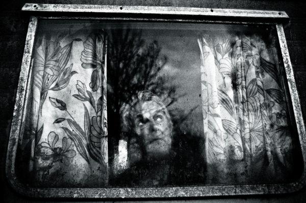 Man achter raam